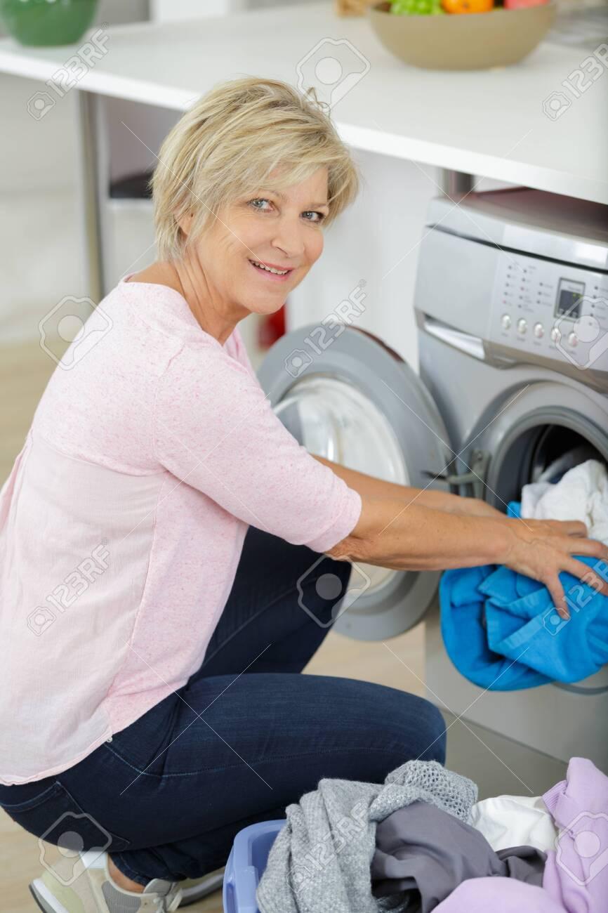 elderly woman doing the laundry - 126476682