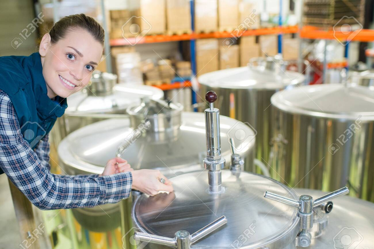 portrait of woman in brewery stood next to vats - 130982239