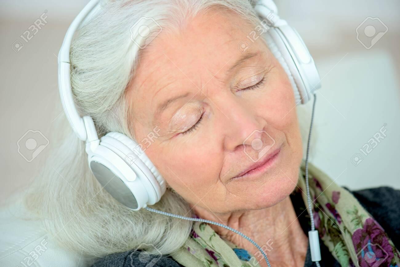 a senior woman in headphones - 134949809
