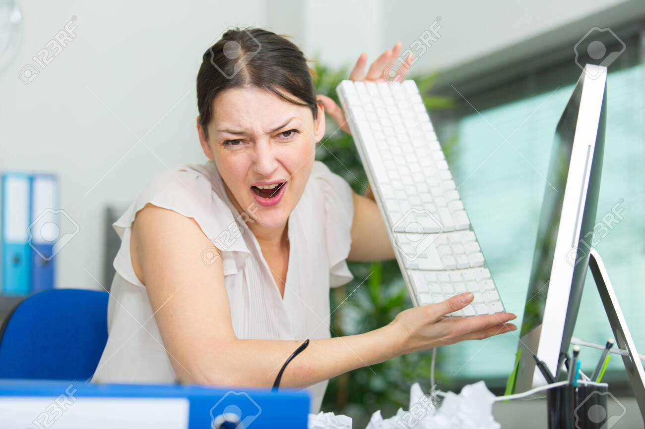 Annoyed and angry woman working on her office desk - 135704698