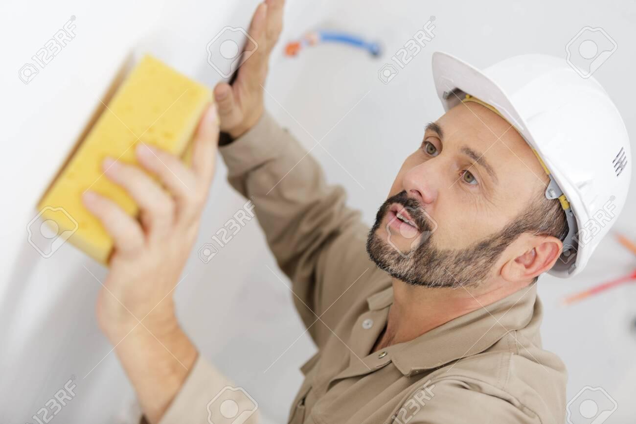 mature builder using sponge on wall - 139350777