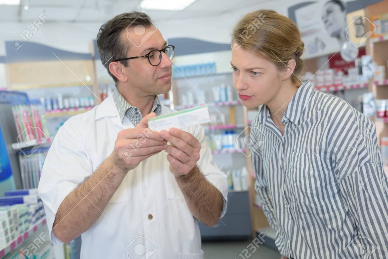 pharmacist and client looking at a product box - 140493612