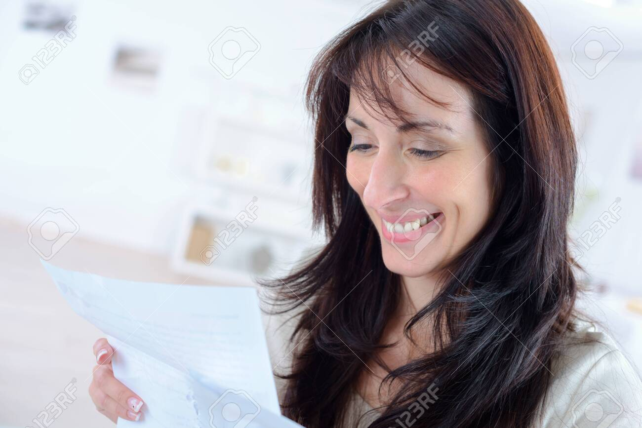 woman reading a letter sitting on a couch at home - 140773984