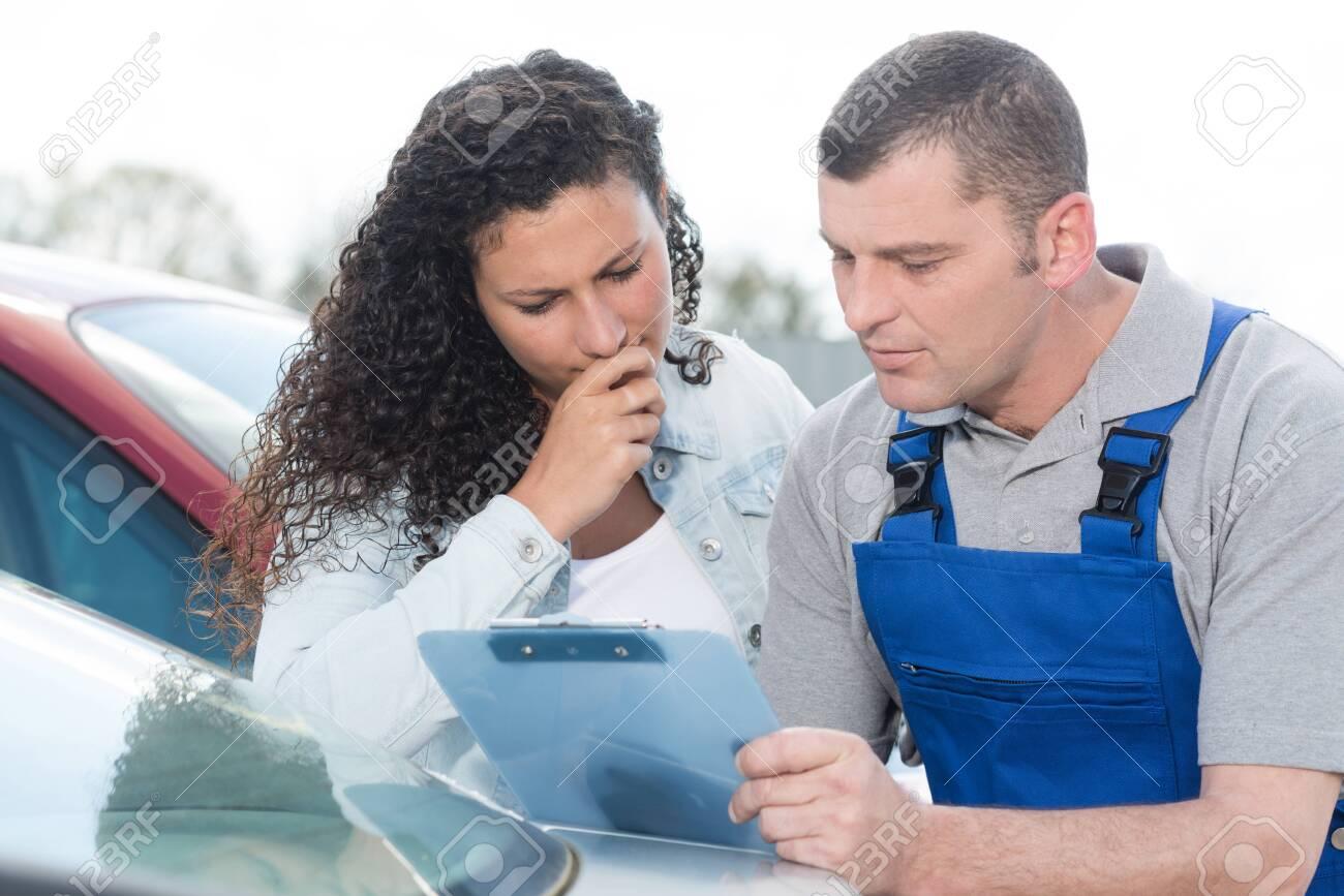 male mechanic and female customer outdoors - 140774482