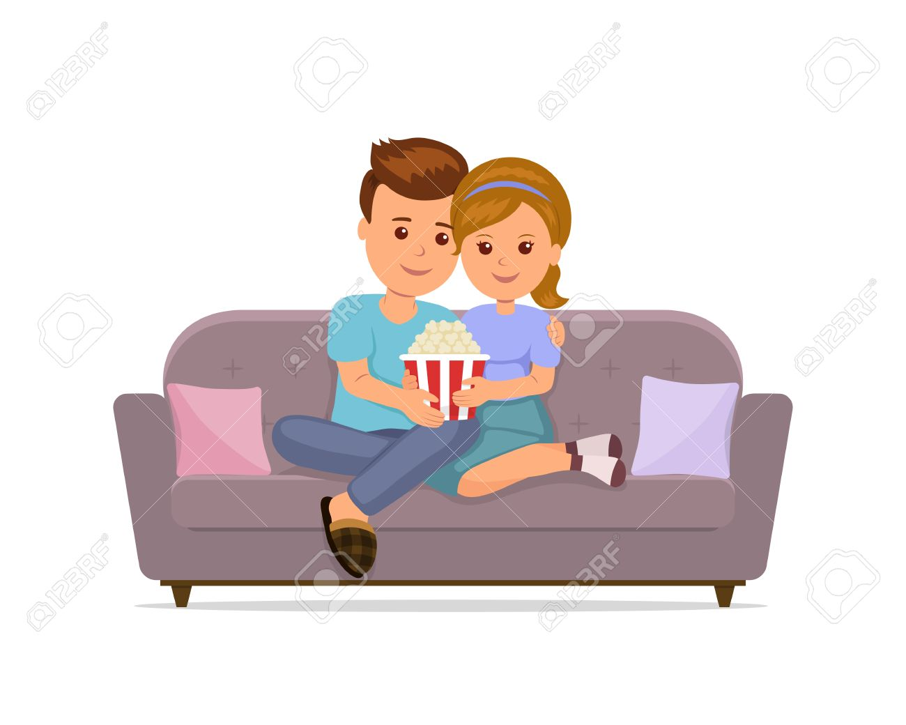 Couple sitting on sofa cuddling, eating popcorn and watching..