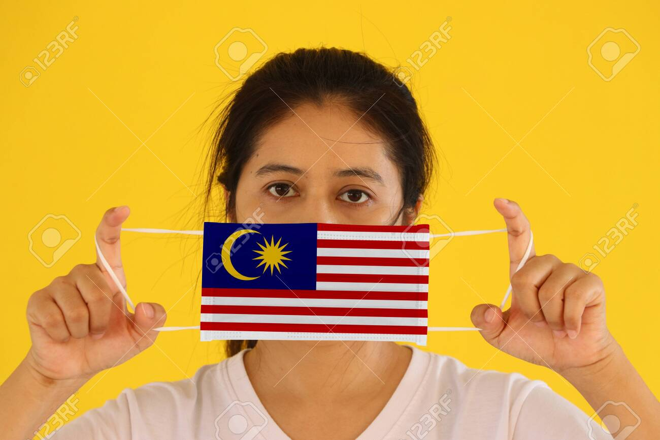 A woman in white shirt with Malaysia flag on hygienic mask in her hand and lifted up the front face on yellow background. Concept of Combating illness. - 151629064