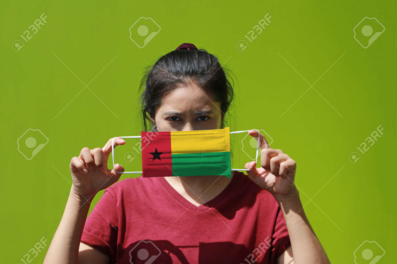 A woman and hygienic mask with Guinea Bissau flag pattern in her hand and raises it to cover her face on green background. A mask is a very good protection from Tiny Particle or respiratory disease. - 158722218