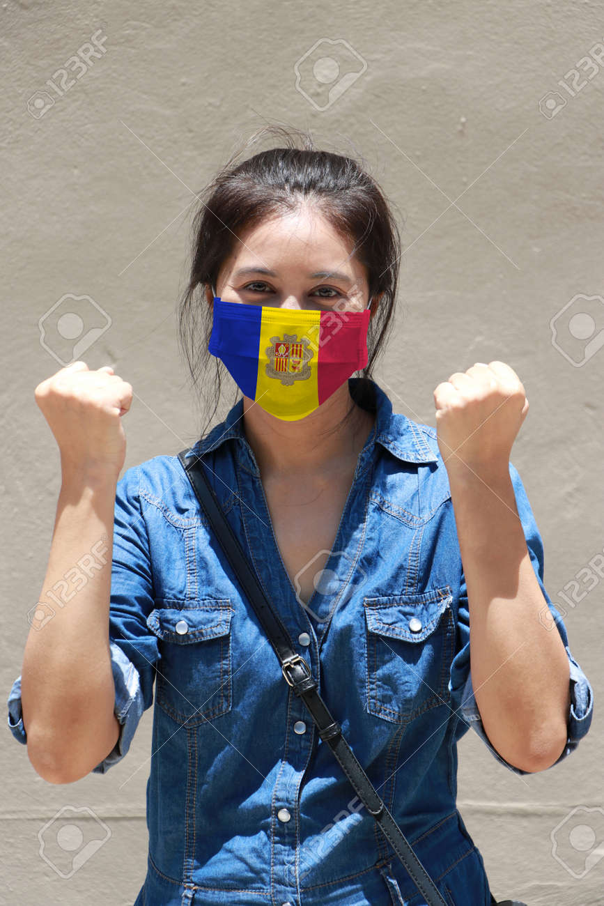 Andorra flag on hygienic mask. Masked woman prevent germs and wear denim dress. Tiny Particle or respiratory disease protection. Concept of Combating illness. - 158803108
