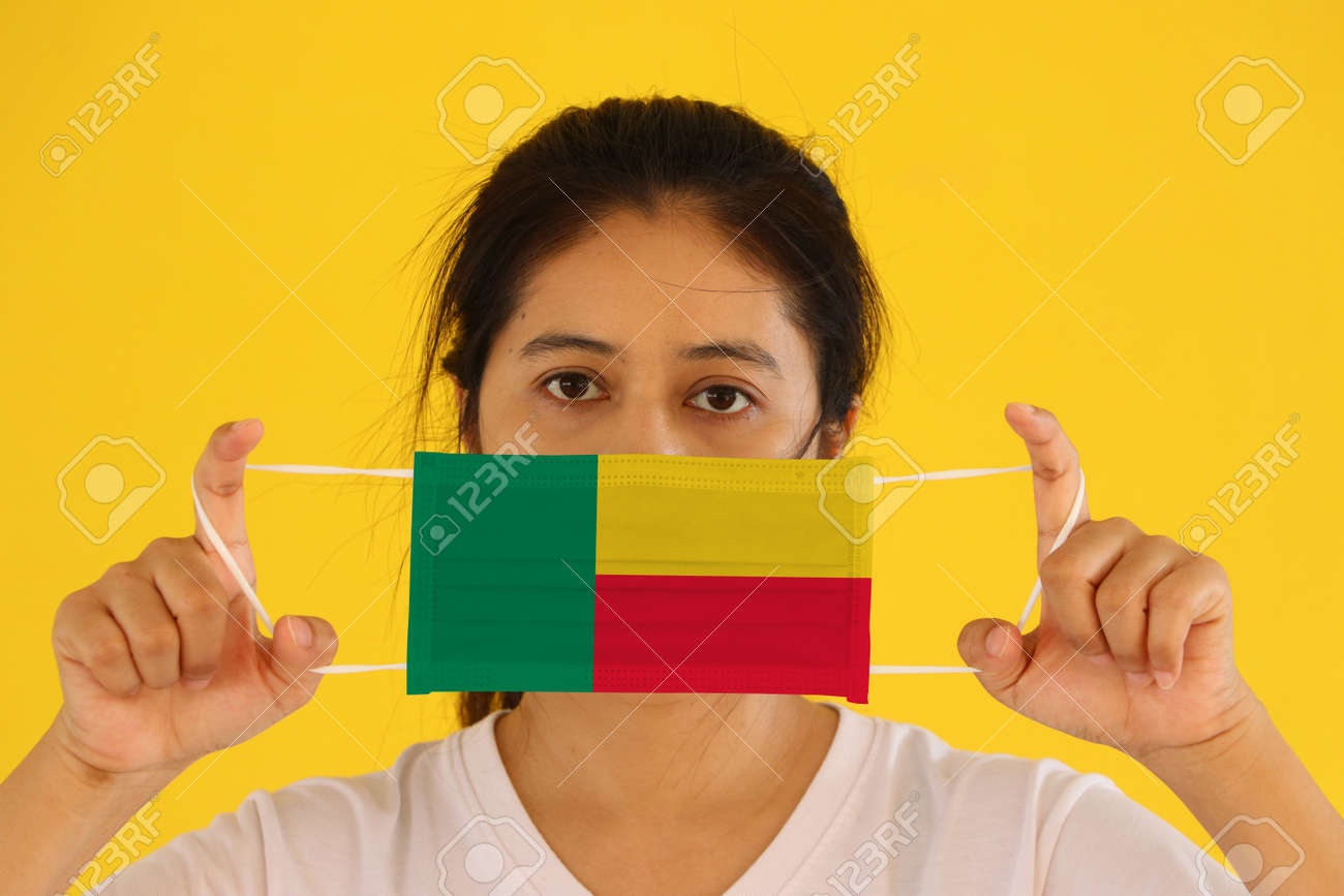 A woman in white shirt with Benin flag on hygienic mask in her hand and lifted up the front face on yellow background. Tiny Particle or virus corona or Covid 19 protection. Concept of Combating illness. - 158803112