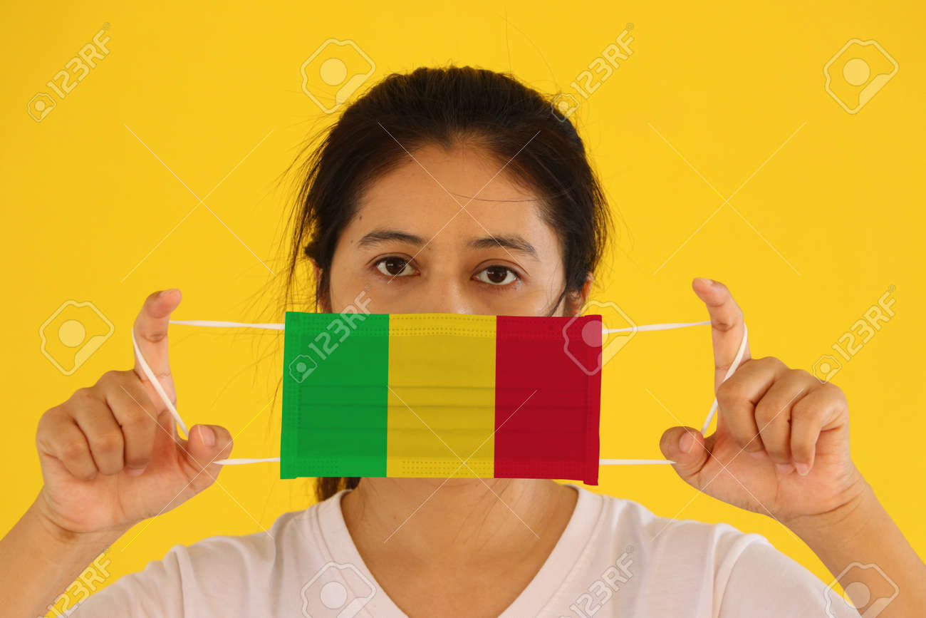 A woman in white shirt with Mali flag on hygienic mask in her hand and lifted up the front face on yellow background. Tiny Particle or virus corona or Covid 19 protection. Concept of Combating illness. - 160156374