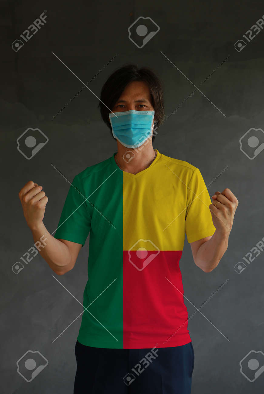 Man wearing hygienic mask and wearing Benin flag colored shirt and standing with raised both fist on dark wall background. Concept of protect tiny dust or disease. - 160156375