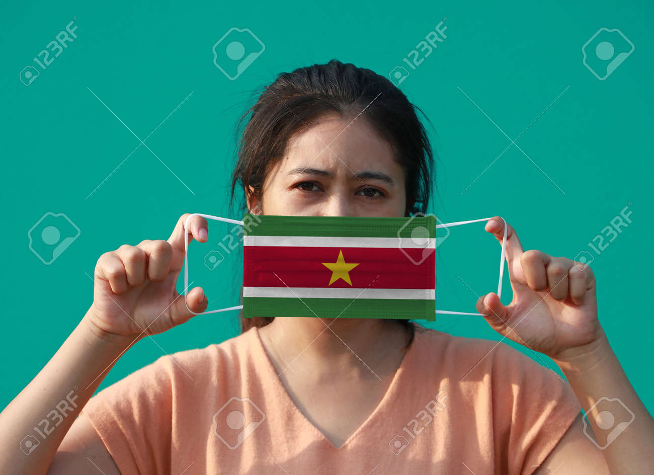 A woman with Suriname flag on hygienic mask in her hand and lifted up the front face on green background. Tiny Particle or virus corona or Covid 19 protection. Concept of Combating illness. - 160156377