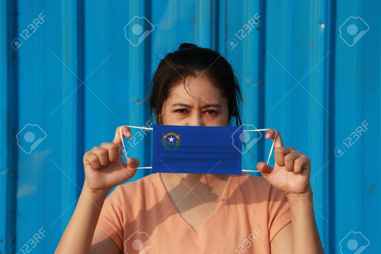 A woman and hygienic mask with Nevada flag pattern in her hand and raises it to cover her face on blue background. A mask is a very good protection from Tiny Particle or virus corona or Covid 19. - 160156378