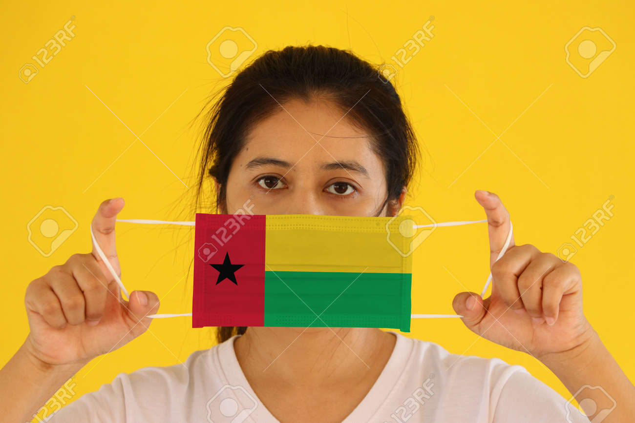 A woman in white shirt with Guinea bissau flag on hygienic mask in her hand and lifted up the front face on yellow background. - 165993609