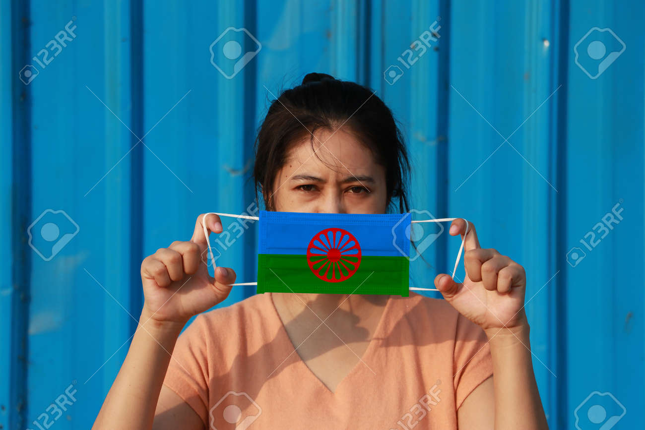 A woman with Romani people flag on hygienic mask in her hand and lifted up the front face on blue background. - 165993613