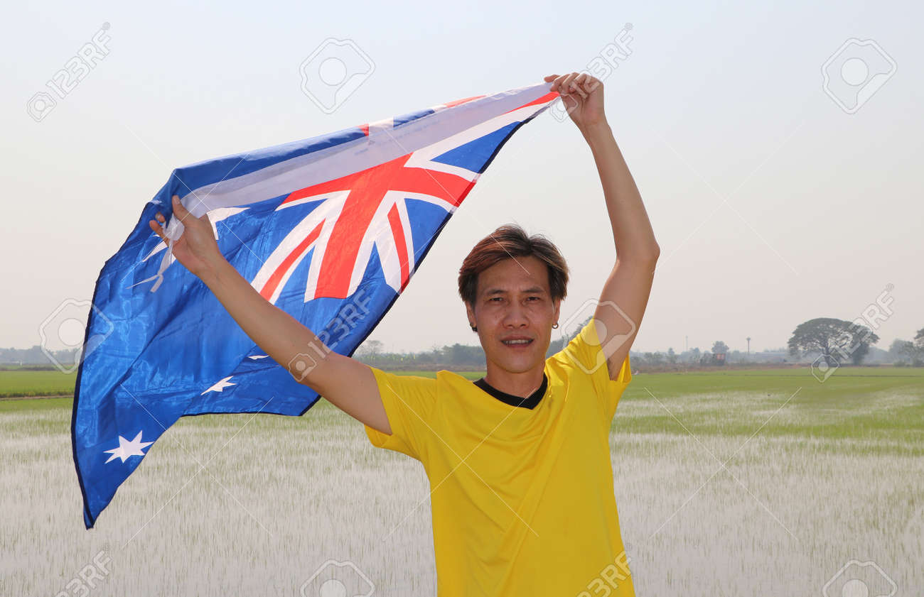 The man in yellow shirt is holding Australia flag in his hands and raising to the end of the arm at the back on nature view and rice fields background. - 163875069