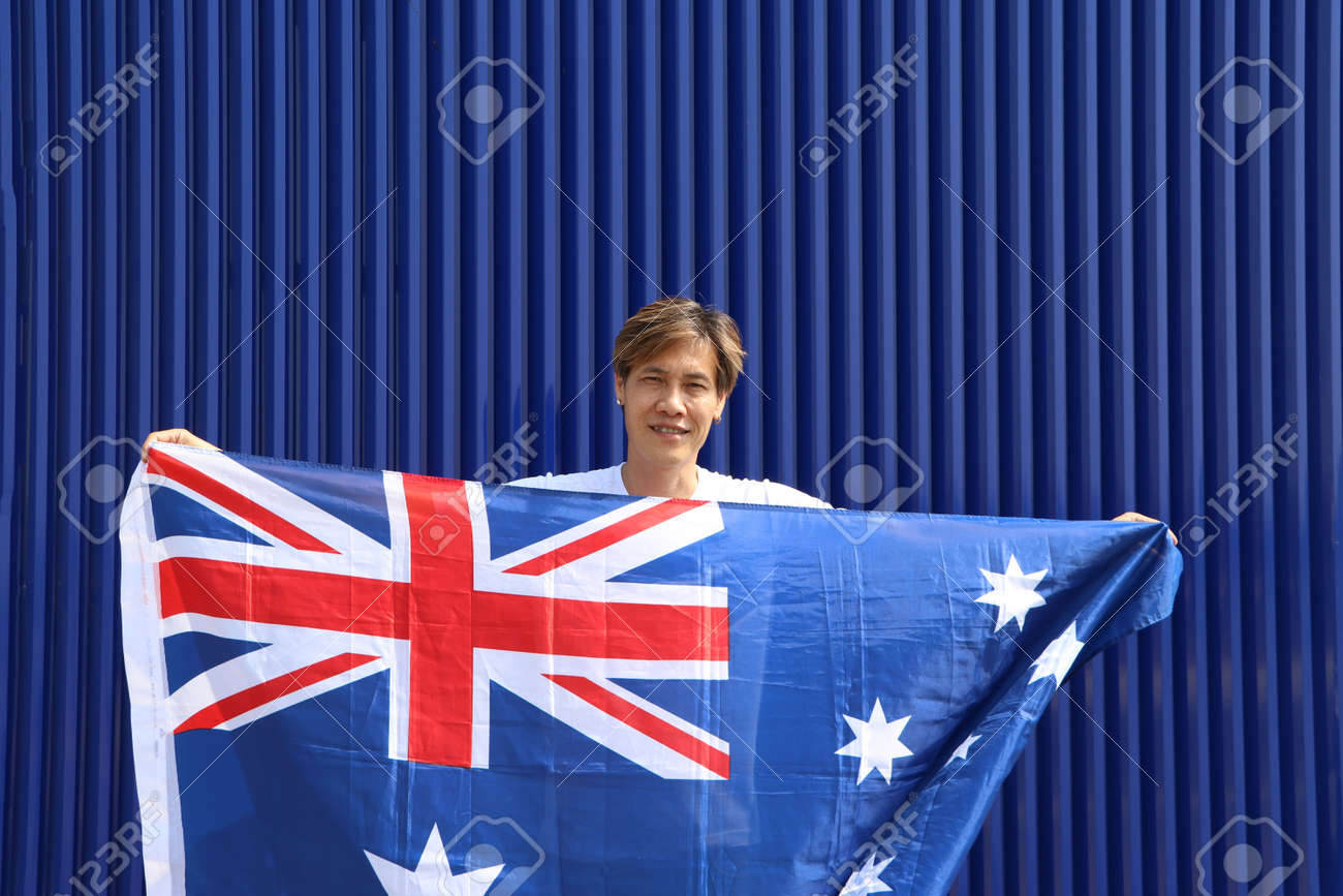 The man is holding Australia fabric flag in his hands on blue background. - 163875071