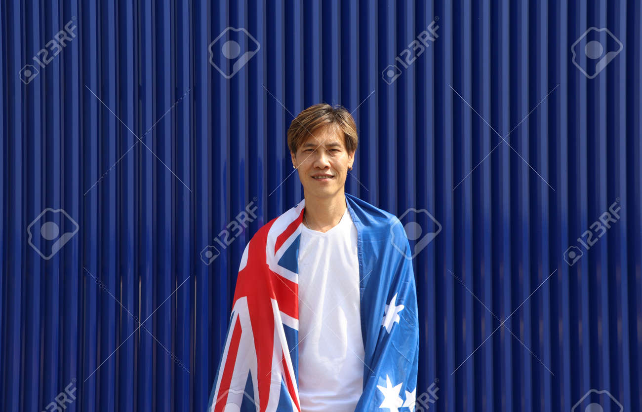 The man in white shirt with Australia flag on his shoulder on blue background. - 163875070