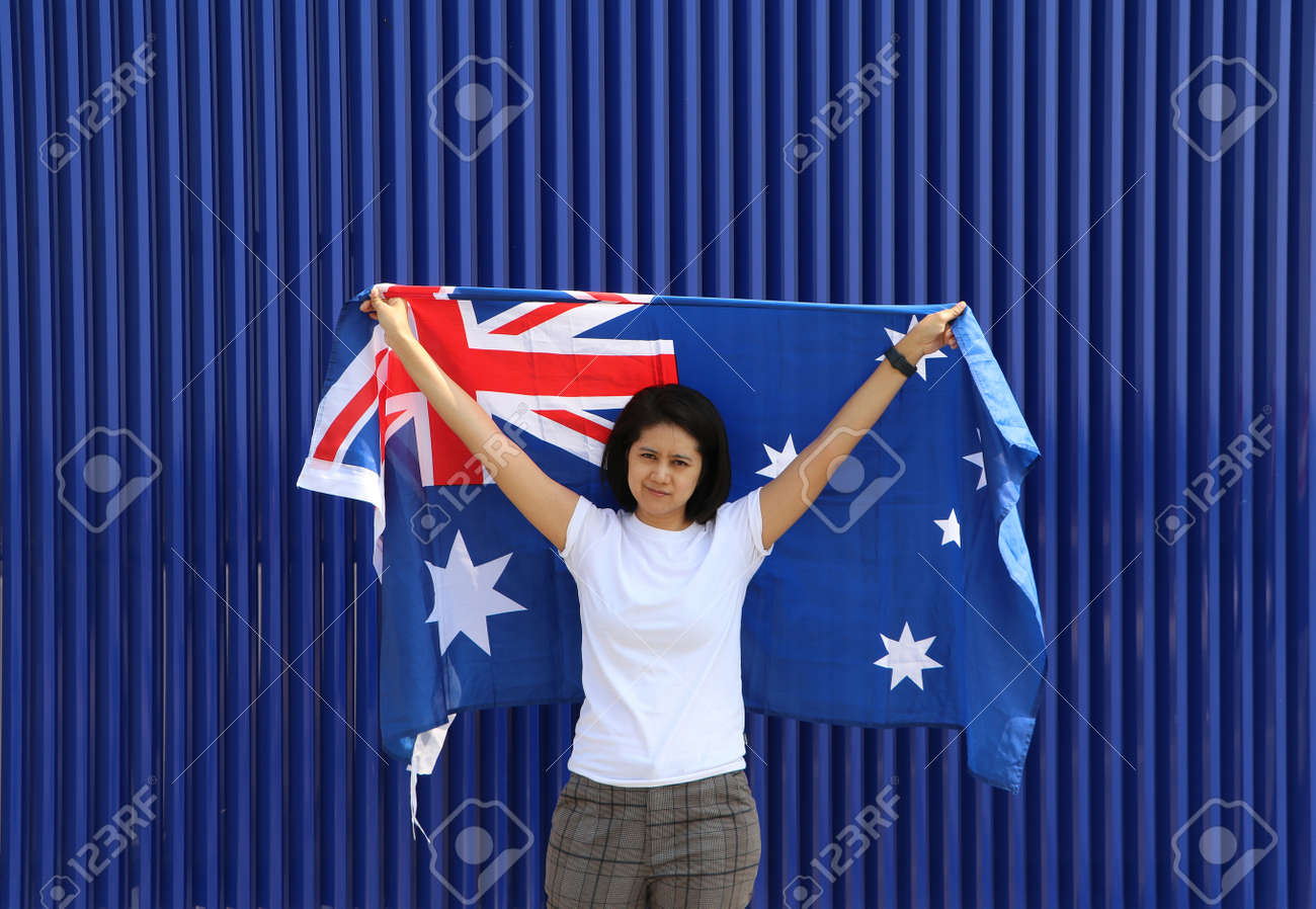 pretty lady is holding Australia flag in her hands and raising to the end of the arm at the back on blue background. - 163875073
