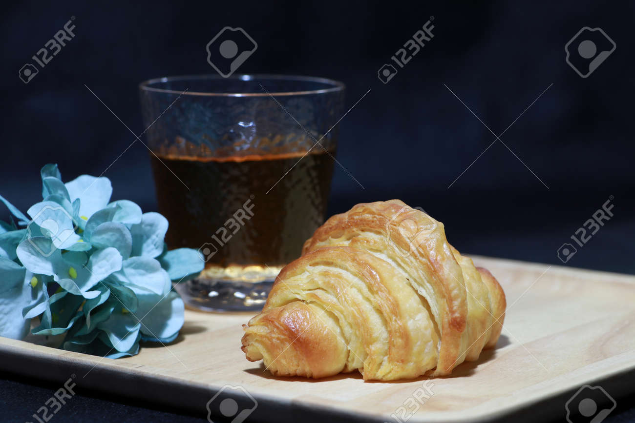 The croissant placed on the square wooden tray with tea in a glass and blue flowers on dark background. It is a French crescent shaped roll made of sweet flaky pastry, often eaten for breakfast. - 163505261