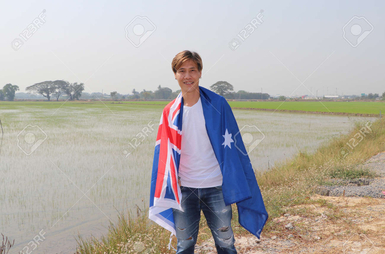 The man in white shirt with Australia flag on his shoulder on nature view and rice fields background. - 164472049