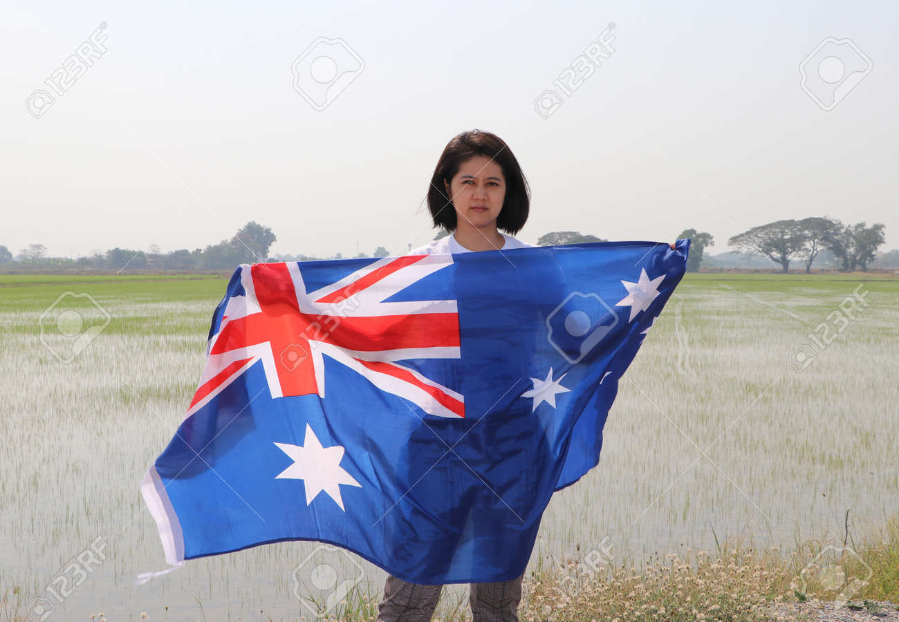 pretty lady is holding Australia fabric flag in her hands nature view and rice fields background. - 164465678