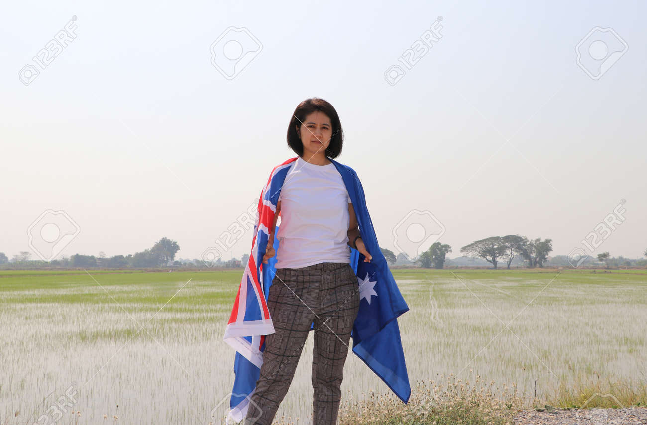 pretty lady in white shirt with Australia flag on her shoulder on nature view and rice fields background. - 164472138
