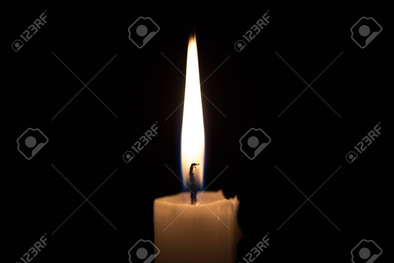 Candle on Black Background - 134742847