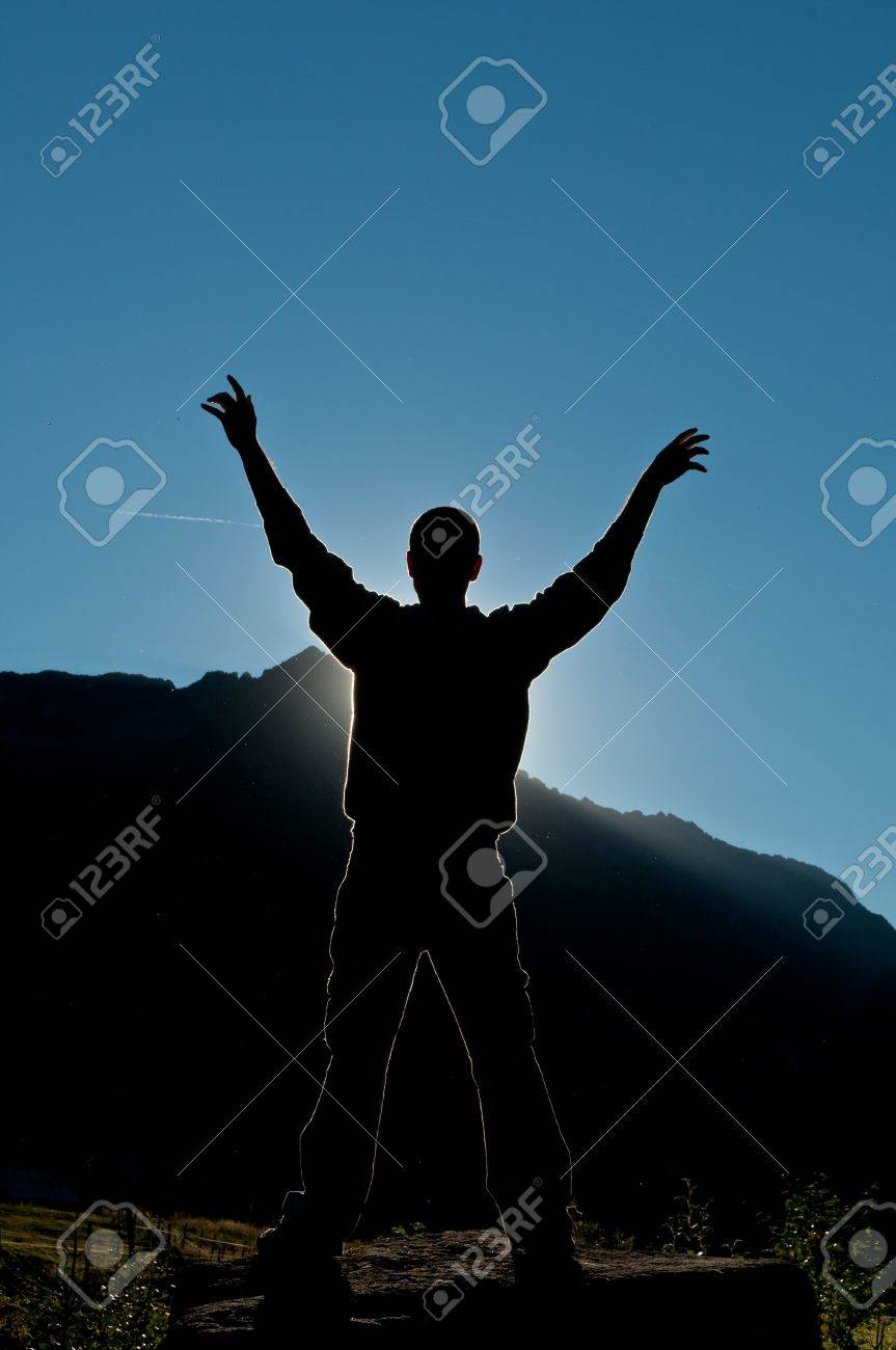 Silhouette of person winning single in the top of the mountain at sunset Stock Photo - 13464356