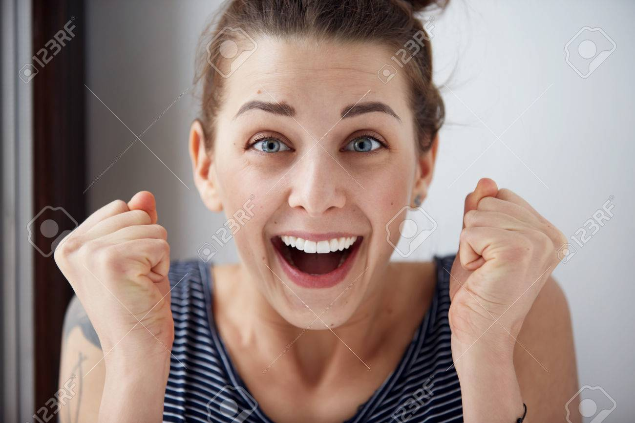 Surprised woman with hands up amazed or shocked by unexpected news holding close palms up and showing happy expression. Young adult woman on greybackground - 51469779