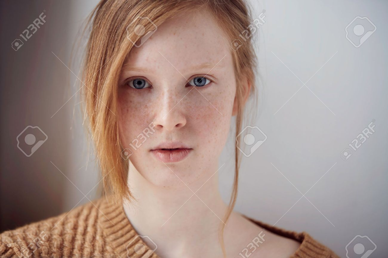 Portrait of beautiful pensive girl with red hair at home. Cute redhead and freckles woman face closeup portrait with healthy skin. - 52008763