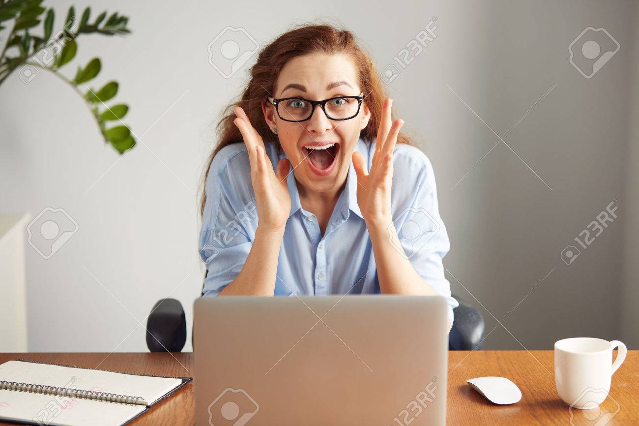 Portrait of a cute redhead girl wearing glasses and blue shirt screaming with excitement and joy while working on her laptop. Headshot of an excited female student with winning expression on her face - 55379315