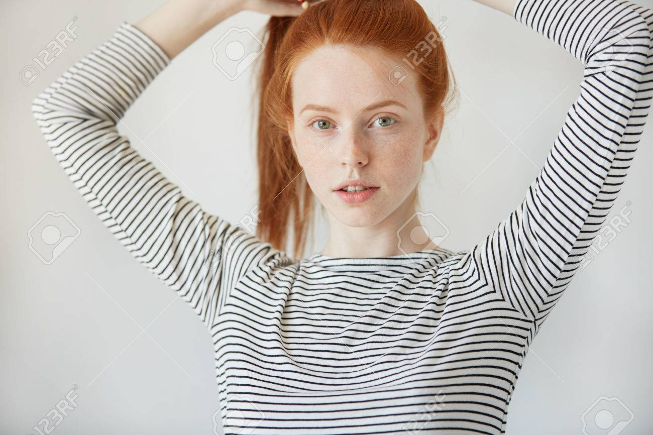 Beautiful Caucasian young woman with healthy freckled skin looking and smiling with thoughtful expression at the camera. Redhead girl wearing striped top posing iolated against white concrete wall - 57646647