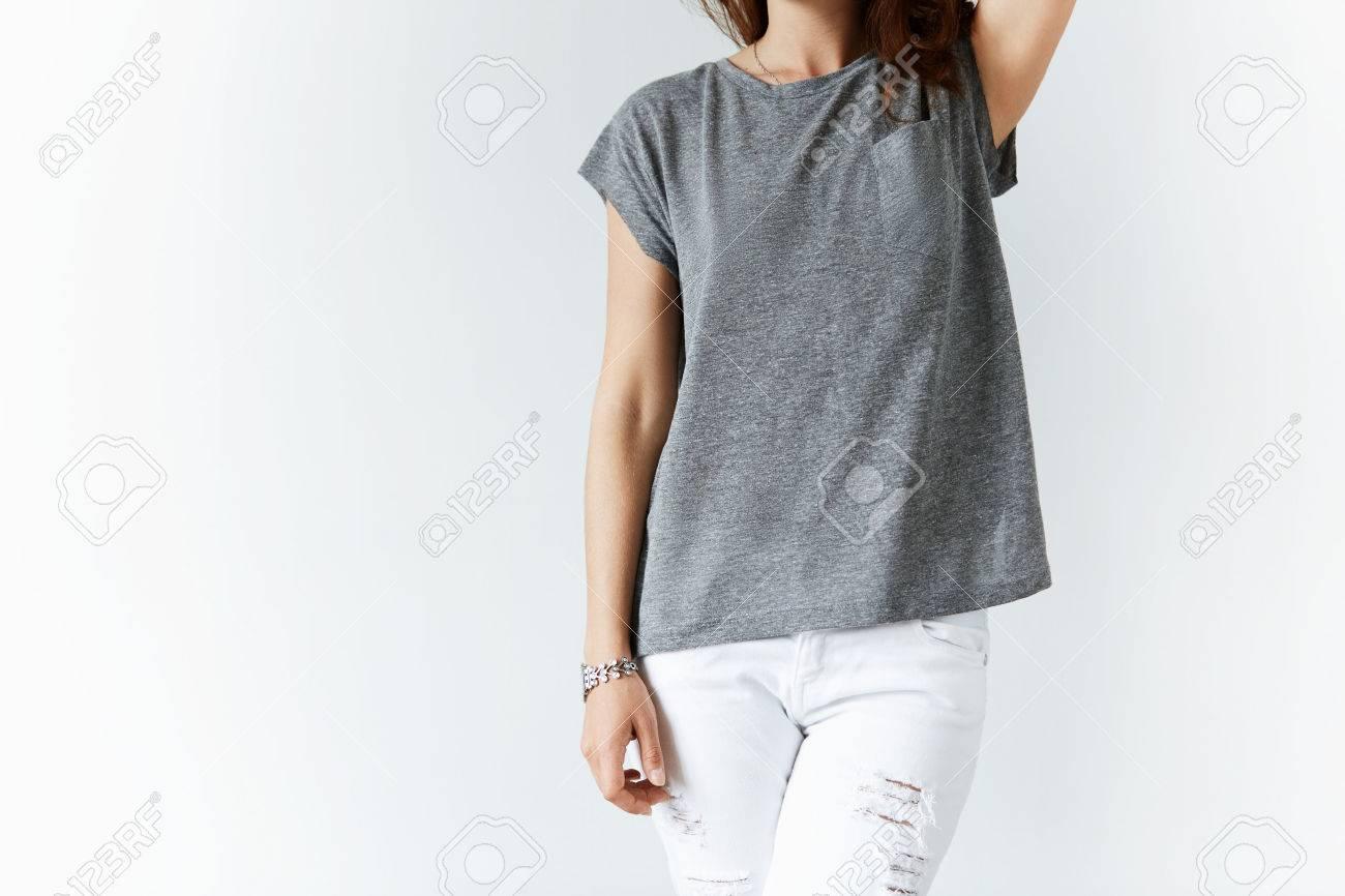 Retrato De Mujer Joven En Pantalones De Mezclilla Y Blanco Camiseta Gris Presentacion Ocasional Contra El Fondo Blanco De La Pared Del Estudio Con Copia Espacio Para El Texto O El Contenido