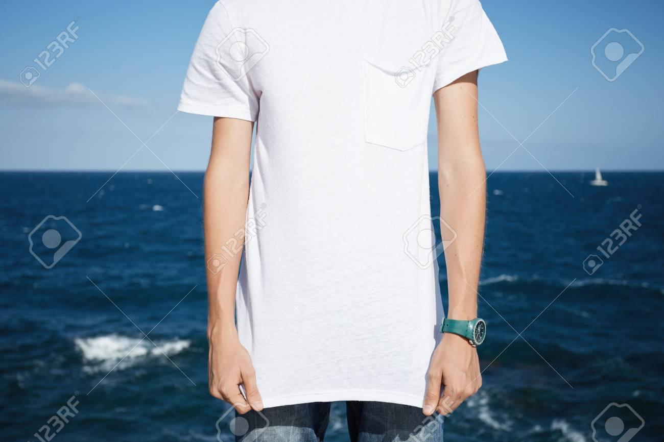 Bijgesneden opname van de jonge blanke man met spijkerbroek en lege witte T shirt met kopie ruimte voor uw promotionele inhoud, tegen blauwe hemel en