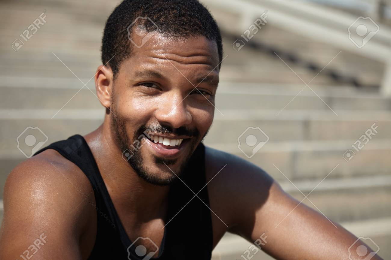 03bf6daa8 Handsome muscular young African runner wearing black sleeveless shirt,  sitting on sidewalks with happy and
