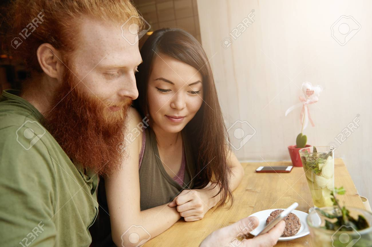 lovely young couple having fresh drinks and dessert at cafe