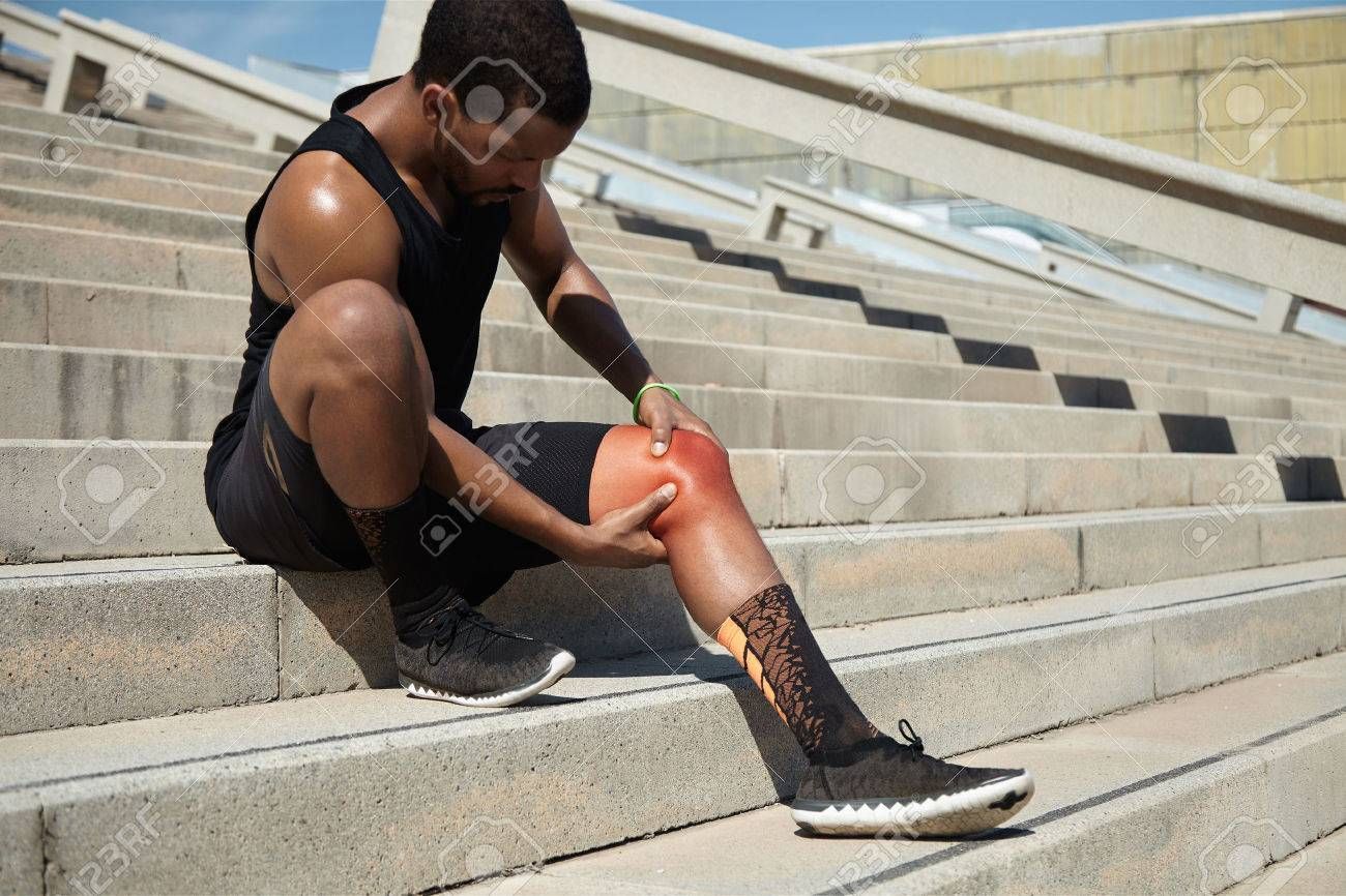 Physical injury concept. Attractive African runner with athletic body wearing black running shoes, sitting on steps on concrete stair, clutching injured knee in excruciating pain depicted in red color - 62999526