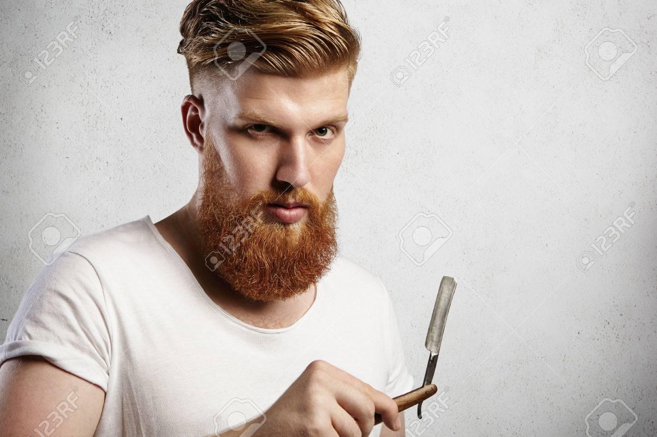 Hombre Inconformista-como De Raza Caucásica En La Camiseta Blanca Tratando  De Decidir Si Se Debe Afeitarse La Barba Larga De Pelo Rojo O No. e4979045c2c1