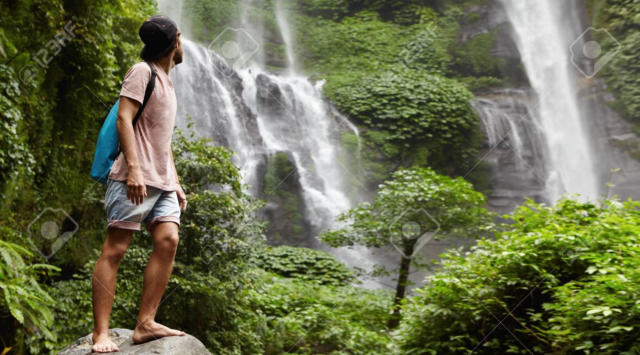 e7aee54f4a1 Stock Photo - Young barefooted tourist in baseball cap standing on big  stone and looking back at waterfall behind him in beautiful exotic nature.  Bearded ...