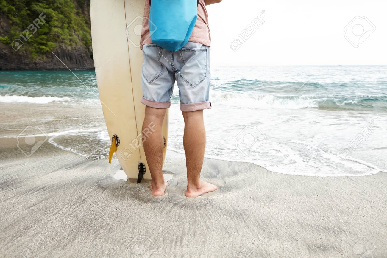 Cropped rear shot of barefooted surfer in jeans shorts standing on wet sand  in front of