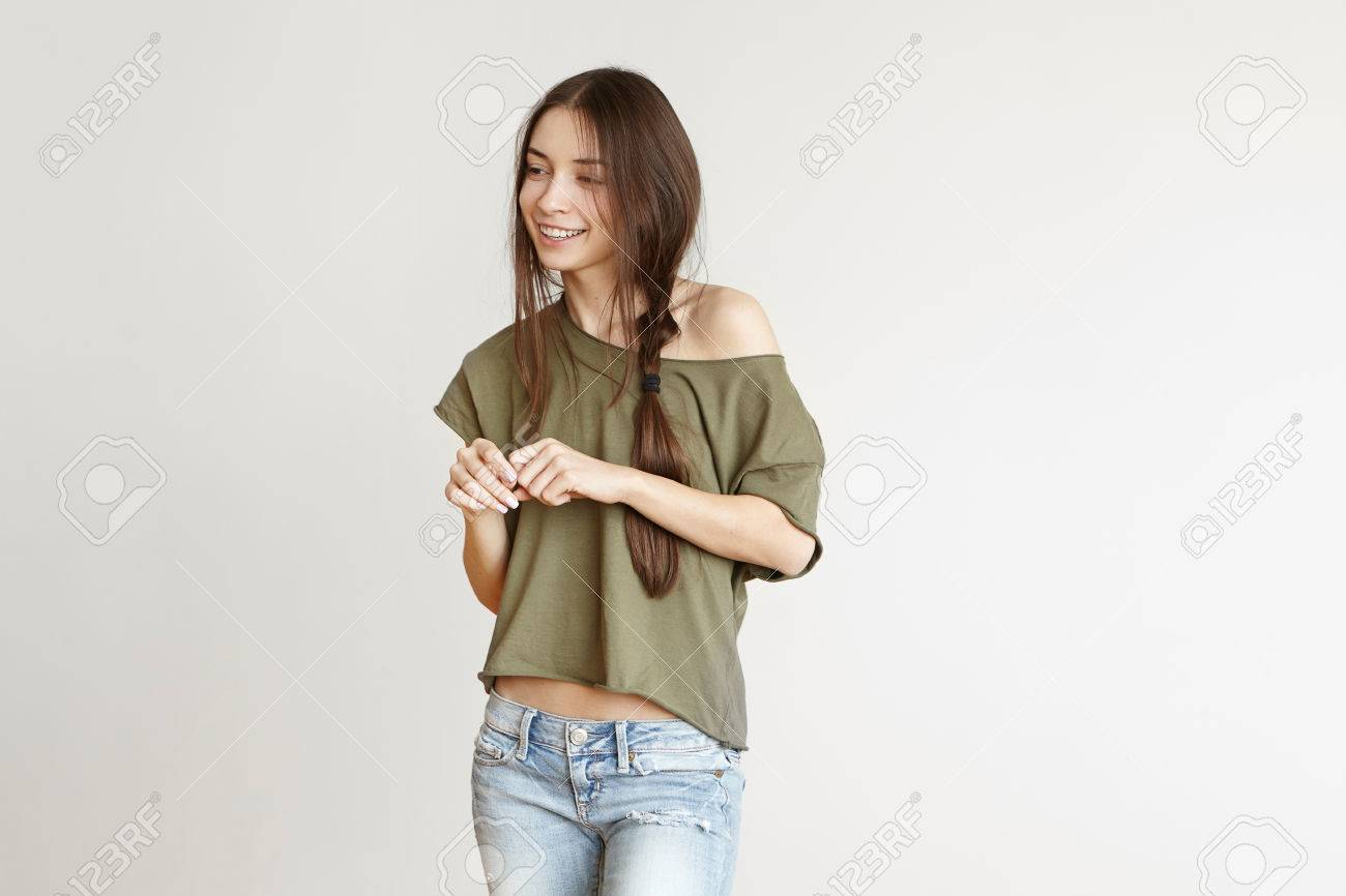 Playful Beautiful Teenage Girl With Messy Hairstyle Wearing Jeans