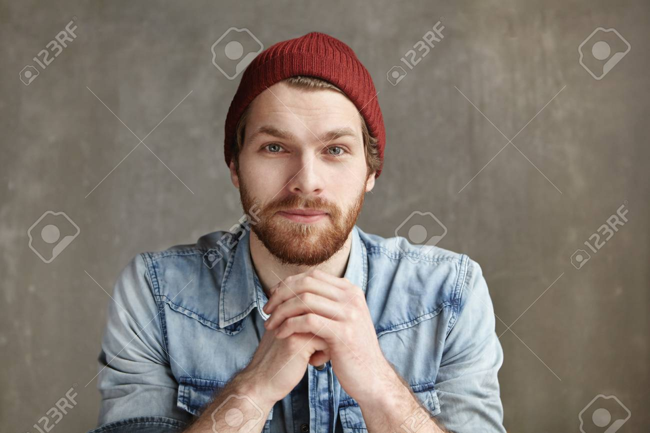 23cc3a986be Headshot of modern good-looking young European hipster wearing stylish hat  and blue jeans shirt