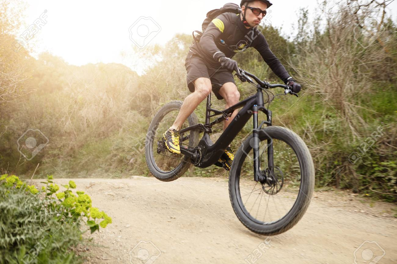 Cyclist in action jumping high on black electric motor-powered bicycle down trail in woods. Young rider wearing glasses and helmet making extreme biking stunt on e-bike while exercising outdoors - 75999077