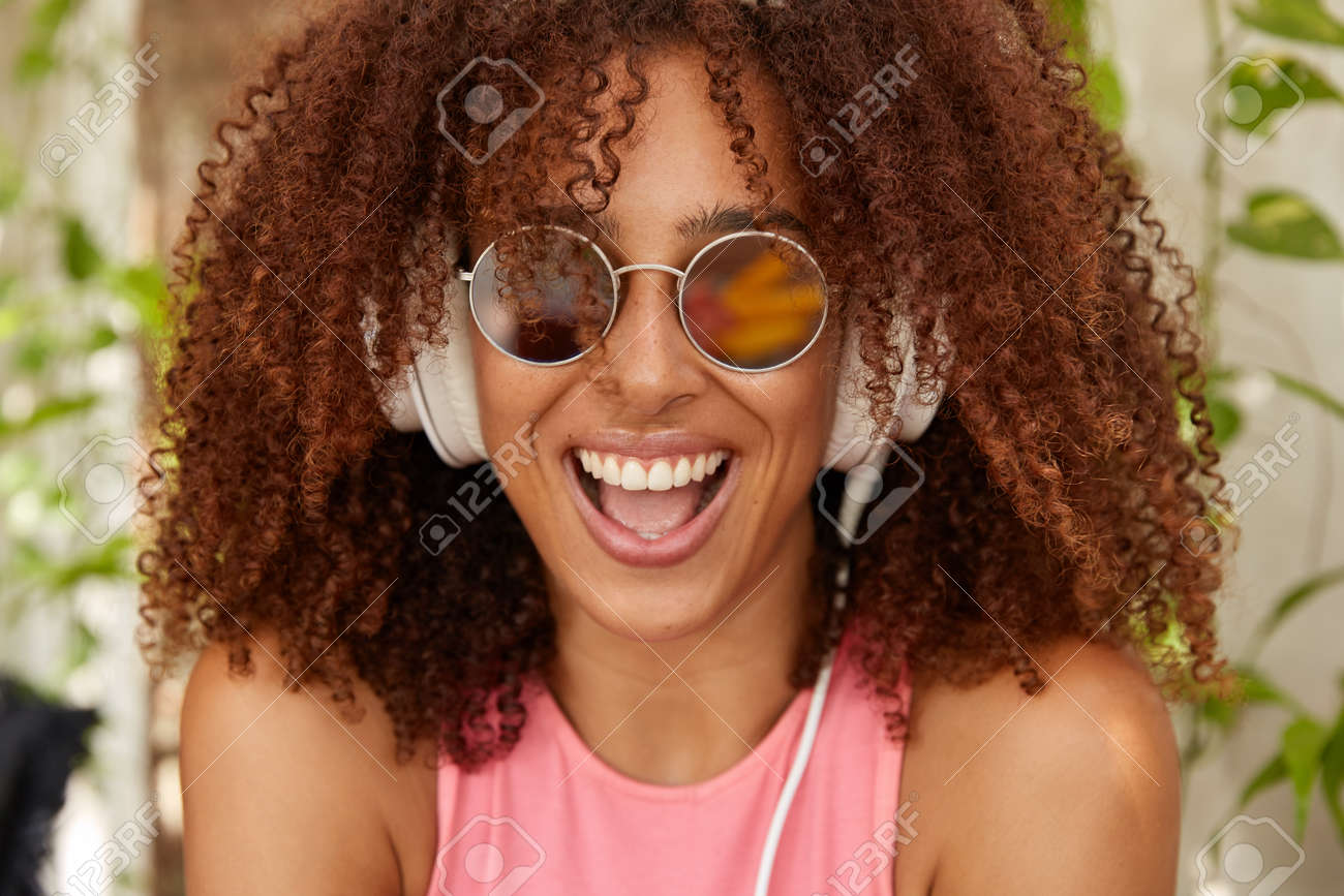 Photo of joyful stylish teenager with Afro haircut, dark skin, opens mouth widely, smiles positively, wears round sunglasses, listens music with new modern headphones, feels content, enjoys melody - 157839501