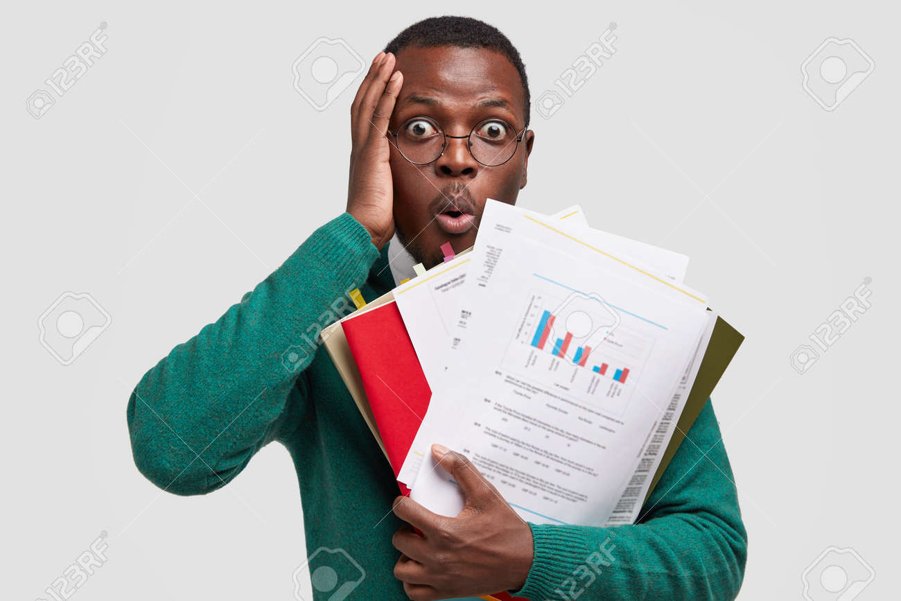 Headshot of puzzled African American man touches head, stares with bugged eyes, opens mouth from amazement, holds paper documents, has deadline for making task, isolated on white studio wall - 158071654
