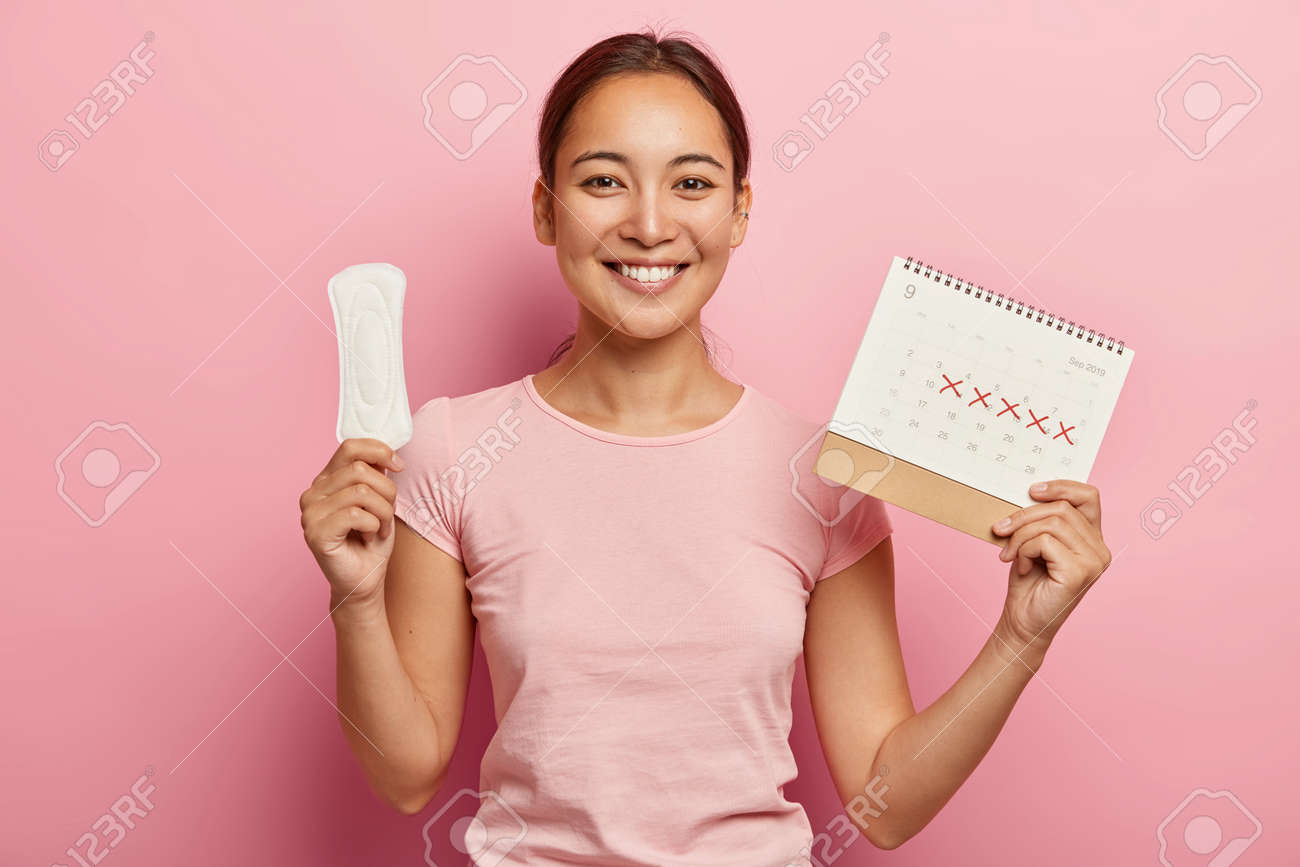 Adorable dark haired korean woman holds clean pad and menstruation calendar, has pleased face expression, happy to have regular menstrual cycle, wears pink t shirt. Women, hygiene, health care concept - 159234955