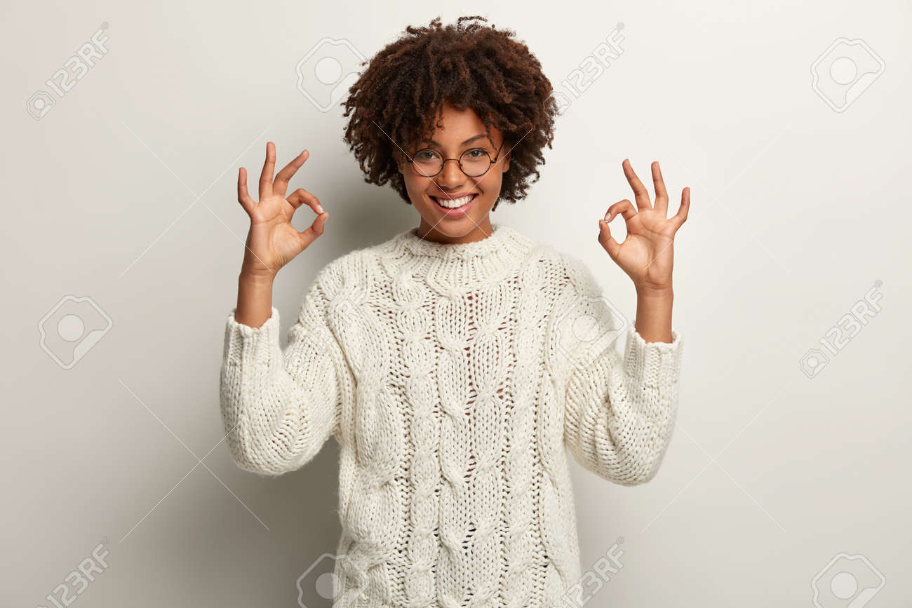 Approval and agreement concept. Picture of happy black ethnic woman makes okay gesture with both hands, says everything is super or perfect, dressed in white jumper, proceeds according to plan - 159250395