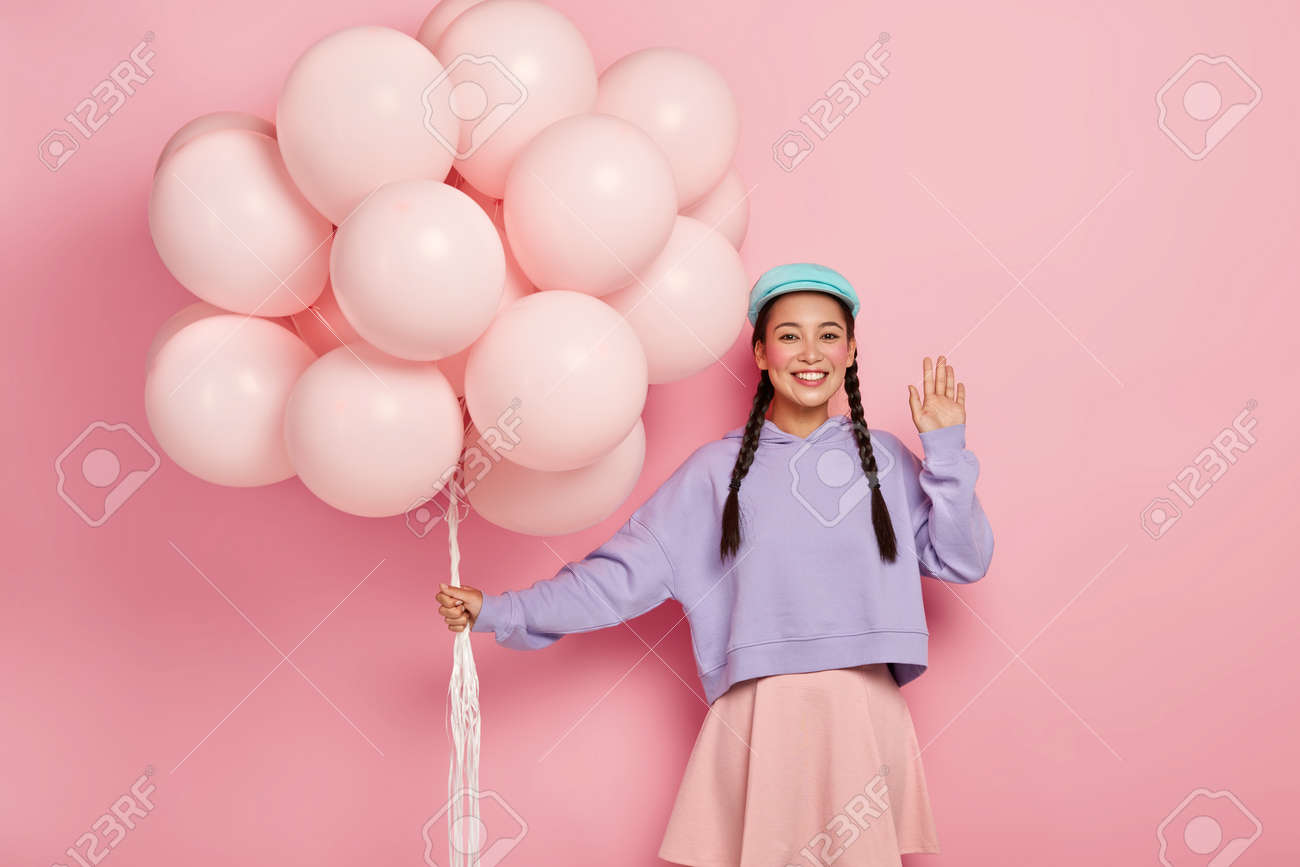 Positive Chinese woman comes on friends birthday party, greets fellows, has dark hair combed in two plaits, dressed in casual outfit, holds helium balloons, poses over pink studio wall - 159304810