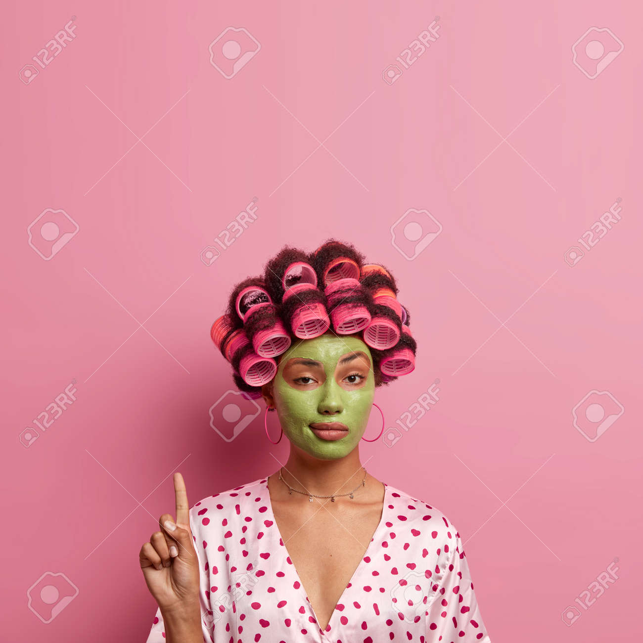 Confident ethnic woman with hair rollers, green facial mask, looks mysteriously at camera, points above, shows copy space for your advertisement, pink background. Beauty, cosmetology concept - 158962132